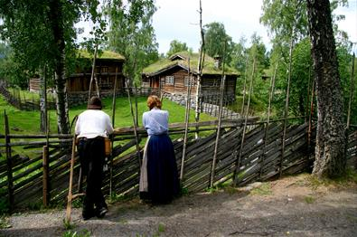Man and woman in old costumes by a wooden fence in front of old timber houses at the open-air museum Maihaugen in Lillehammer in Norway.